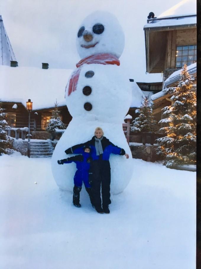 Елена със сина си на фона на гигантски снежен човек в Лапландия
