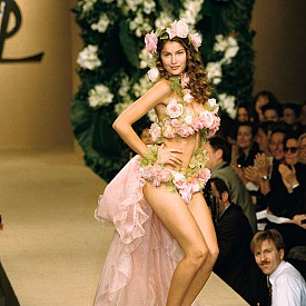 """Може би най-революционната сватбена визия на маестрото е тази с розите. Сен Лоран прикепи цветя по тялото на Летисия Каста. Булката (по-скоро, """"кралицата на елфите"""" или """"богинята на гората""""), се появи по време на дефилето за Haute couture пролет-лято 1999 в Париж. Летисия е една от любимите музи на Ив Сен Лоран и е закривала десет от шоутата на модната марка в ролята на булката."""