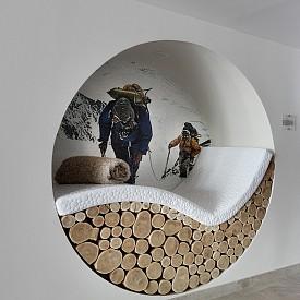 """С фототапет и малко архитектурна намеса в някоя от стените може да си направите уютен кът за релакс и четене, който да ви """"пренася"""" в облаците. Дизайнерите на Pashmina са използвали естествени дървени трупи за повече уют."""