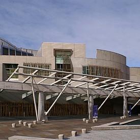 """Изграждането на основната сграда на органа на властта в Шотландия е започнало през 1999 г. (след референдум през 1997 г.), а финалът е едва през 2004 г. Архитект на конструкцията е каталунецът Енрик Миралес, който е починал през 2000г г. Строежът на сградата струвал 10 пъти повече (414.4 милиона паунда) от заложения първоначално (55 милиона). Това провокирало недоволството на обществото. Освен това сградата заела и 29-то място в списъка с """"30-те най-грозни архитектури"""" на изданието Telegraph."""