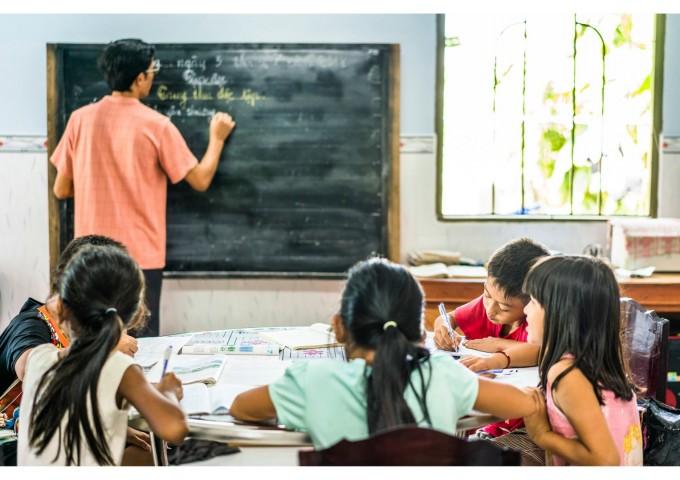 Учител, който преподава допълнителни уроци на децата в дома си, по време на лятната ваканция във Виетнам