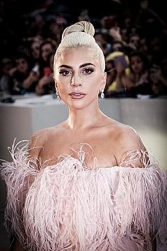 """ЛЕЙДИ ГАГА – ШАПКИ ГОРЕ: Да се кандидатираш за стажант, когато си на върха на кариерата си, е доста необичайно. Такава е и 6-кратната носителка на """"Грами"""". През 2010 г., едва 23-годишна, тя изявява желание да стане сътрудник на популярния дизайнер на шапки Филип Трейси.  За да си извоюва това право, се налага Лейди Гага да докаже шивашките си умения на моделиера, чиито произведения красят главите както на кралски особи, така и нейната собствена."""