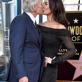 """ДА СИ ПРИПОМНЯМЕ НАЧАЛОТО • Майкъл Дъглас и Катрин Зита-Джоунс • Женени от: 18 години • Наскоро актрисата припомни първата им среща през 1998 г. на филмовия фестивал в Довил, Франция. Тогава Катрин е на 28, а секссимволът на американското кино вече е 53-годишен. Въпреки възрастовата разлика, тя е запленена от неговия чар. В свой Instagram пост под снимка от Довил актрисата пише: """"Първата ми среща със съпруга ми. Не мога да си спомня за какво говореше"""". В свой пост за годишнината от сватбата им пък казва: """"Навремето мислех, че в живота ми няма да има по-хубави дни, но съм грешала."""" Според Катрин причината за техния дълъг и успешен брак е, че двамата се вслушват един в друг: """"Имам прекрасен съпруг, който се вслушва в моето мнение, а аз се вслушвам в неговото. Така всичко си дойде на мястото."""""""