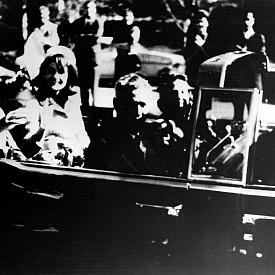 """Отказва да съблече розовата рокля в деня на покушението на президента. На 22 ноември 1963 г. Джаки седи в колата до съпруга си при обиколката им в Далас, когато куршум пронизва сърцето му и той умира. Розовият костюм, с който е облечена е целият в кръв. Тя обаче го носи в момента, в който Линдън Джонсън е обявен за новия президент на САЩ. На въпроса не иска ли да се преоблече, Джаки казва: """"О, не, искам всички да видят какво направиха на Джак."""" Днес тоалетът с кървавото петно е в Националния архив, но не и шапката й, която се губи в деня на покушението."""