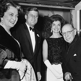 """Стилът й едновременно буди възхищение и предизвиква критики. Тя е определяна от мнозина за модна икона и стилът й и до днес е копиран от милиони жени. """"Jackie look"""" се превръща в тренд, като хиляди магазини предлагат тоалети подобни на нейните. Желанието й да притежава дрехи от големи френски марки обаче й носи и много критики. Това особено много се случва на президентската кампания през 1960 г., като след като става Първа дама започва да се притеснява, че модният й вкус може да отдалечи семейството от останалите американци, тъй като носи чуждестранни марки. На помощ идва тъст й, който я запознава с дизайнера Олег Касини, който моделира 300 от най-известните й тоалети."""