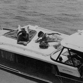 """Елизабет Тейлър и Ричард Бъртън– прясно влюбени след снимките на първия им съвместен филм """"Клеопатра"""" и все още женени за други брачни партньори, са изловени от папараци на борда на яхта край остров Иския, Италия, през лятото на 1962г."""