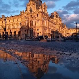 Лувърът изглежда доста романтично на залез слънце в отражението на локвите