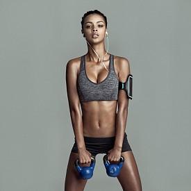 """УПРАЖНЕНИЯ С ДЪМБЕЛИ Тези упражнения ангажират цялото тяло, а изпълнявани с висока интензивност, изгарят и много калории. Застанете изправени и хванете с две ръце дъмбела пред тялото. Наведете леко торса. Натискът трябва да е върху бедрата – залюлейте тежестта и я вдигнете над главата. След това я върнете обратно. Направете 3 серии с по 15 """"люлки""""."""