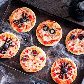 ХЕЛОУИНСКИ МИНИ ПИЦИ За финал нещо солено. Продукти: 1 пакет охладено тесто, 1 чаша доматен сос, 1.5 чаша настъргано сирене или кашкавал, 1/2 чаша черни маслини. Приготвяне: Загрейте фурната на 200 градуса. Подгответе лист хартия за печене. Разстелете тестото върху плота. С чаша изрежете малки кръгове и ги поставете върху подготвената хартия. Намажете всеки кръг с доматения сос и отгоре поръсете със сиренето. Използвайте маслините, за да декорирате. Печете 8-10 минути.