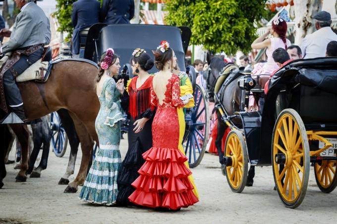 Севилки, облечени с традиционни фламенко рокли по...