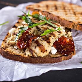 Вечеря – сандвич с пилешко и рукола Препечете 2 филийки пълнозърнест хляб (тост) и намажете с 1 ч. л. нискомаслено прясно сирене (2 % масленост). Измийте, подсушете и накъсайте една шепа салата рукола и я посипете върху едната филийка. Отгоре сложете 30 г пушено или варено пилешко бяло месо от гърдите и захлупете с другата филийка. Към сандвича си пригответе една чаша пресен сок от 1 голям домат, овкусен с малко сол, черен пипер и босилек.  Около 250 калории
