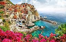 """Приказното цветно градче Манарола е сгушено в земите на Чинкуе Тере (буквално """"Петте земи""""). Намира се на каменистото крайбрежие на Италианската Ривиера. В трудно достъпния район навремето хората са успели да построят пет селища върху скалите, които днес са включени в списъка на ЮНЕСКО. Уникално красиво и фотогенично място, което обаче не става за излежаване на пясъчния плаж, защото такъв не съществува!"""