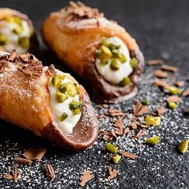 Buongiorno Sicilia! Един от най-вкусните италиански десерти безспорно са сицилианските Каноли. Най-прочутото сладко изкушение на италианския остров представлява тестена фунийка, която се пълни пред очите ви със смес от свежа рикота, мед, плодове, шоколад и шамфъстък - истинска калорична бомба! Можете да ги откриете в почти всяка пастичерия в Италия, но най-вкусните са на самия остров.
