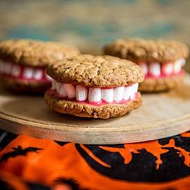 ЗЪБИТЕ НА ДРАКУЛА Можете да използвате бисквити тип cookies. Ще са ви необходими и бонбони маршмелоу, ванилова глазура и червена сладкарска боя. Ваниловата глазура се приготвя с 2 ванилии, 150 г пудра захар, 1 белтък, 1 ч.л. лимонов сок по желание: Ванилията се пресява с пудрата захар и се разбива с белтъка, докато сместа побелее. По желание може да се добави лимонов сок. Сложете и 1/4 ч.л. червена боя за сладкиши, за да оцветите ваниловата глазура. От инструкции нямате нужда, снимката е достатъчно красноречива. Филирани бадеми можете да добавите между парчетата маршмелоу, за да получите вампирски зъби.