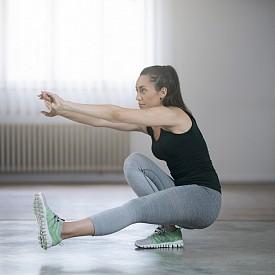 """4) НЕПЪЛЕН КЛЕК НА ЕДИН КРАК:  Застанете прави с гръб към стол или пейка. Изнесете единия крак напред – изпънат и в контрашпиц, а с другия клекнете бавно, опитвайки се да докоснете пейката с дупе, без да сядате на нея. Коленете остават в една линия през цялото време, а тежестта на тялото е върху петата на опорния крак. Изправете и повторете 10 пъти с всеки крак. РАЗНОВИДНОСТ: Когато овладеете клякането до опора (стол или пейка), можете да пробвате и упражнението """"Пистолет"""". Правите пълен клек (до пода), като този на снимката."""