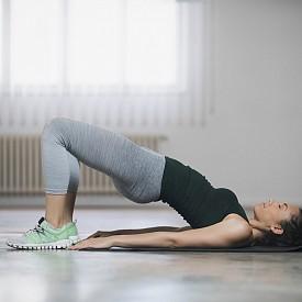 2) ГЛУТЕУС МОСТ: Легнете по гръб със свити колене и леко разкрачени крака. Повдигнете дупето нагоре, така че гърдите, коремът и бедрата да оформят права линия чак до коленете. Задръжте 2-3 секунди, като се фокусирате върху стягането на глутеусите. Върнете дупето на пода. Повторете 20 пъти.