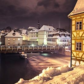 БАМБЕРГ, ГЕРМАНИЯ Севернобаварският град привлича със своята стара част, която е включена в наследството на ЮНЕСКО, с традиционната си раух бира, коледни базари и приказна атмосфера. Сградата на Кметството (Altes Rathaus), построена през XIV век, се намира на остров в река Редниц. Ако преминете по моста, който води до него, ще попаднете в Средновековието – къщи с типичния градеж с дървена рамка и тухли, романска катедрала от XI век, дворци, дворчета и алеи. След като задължително разгледате големия коледен базар на Maximiliansplatz, опитайте и местния специалитет Rauchbier – пушена бира.