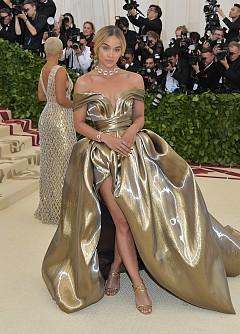 Моделът и актриса Жасмин Сандърс бе облечена с обемна рокля от златисто-бронзово метално ламе. Роклята е с лека драперия върху раменете и елегантна тънка талия. Драматичната обемна пола с дълга цепка разкриваше прелестните крака на Жасмин, акцентирайки върху модерната лекота.