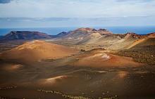 ЛАНСАРОТЕ, КАНАРСКИ ОСТРОВИ -  Уникалните забележителности на Лансароте са черните пясъци по плажовете и наподобяващите на лунната повърхност пейзажи. Национален парк Тиманфая е с най-големия впечатляващ вулканичен пейзаж – на естествената топлина на пясъка може да си сготвите дори храна.