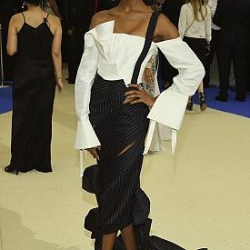 Моделът Джордан Дън носи рокля, извиваща се около тялото и вдъхновена от темата за деконструиране и игра с традиционните похвати в мъжкото облекло. Горната част от копринена тафта създава илюзията за небрежно падаща риза, а полата от ленти от класическо мъжко тънко райе, завършва с големи декоративни пандели. Актрисата Саша Лейн е в прозрачна рокля от структурирана мрежа, декорирана с различни по големина точки – един от основните мотиви при Kawakubo.