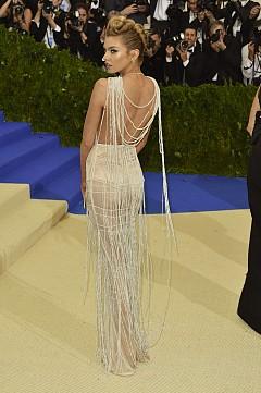 Моделът Стела Максуел носи прозрачна рокля от органична коприна, покрита в перли. Започващи като драпирано колие, украсяващо отворения гръб, перлите продължават около тялото, създавайки движение.