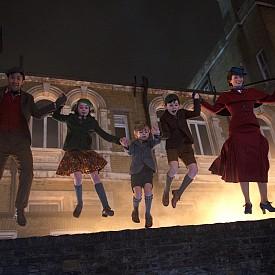 """В """"Мери Попинз се завръща"""" бавачката с магически способности се завръща, за да помогне на следващото поколение в семейство Банкс да намери отново радостта и щастието в живота. Действието във филма се развива 24 години след оригинала. Майкъл Банкс работи в същата банка, в която е работил и баща му, и продължава да живее на ул. """"Черешово дърво"""" 17 с трите си деца – Анабел, Джорджи и Джон. Джейн Банкс пък, също като майка си, се бори за правата на работниците и помага на семейството на брат си, след като съпругата му умира. Точно в този тежък период се появява Мери Попинз и връща радостта и щастието в живота на Банкс. Гледайте от 21 декември по кината."""