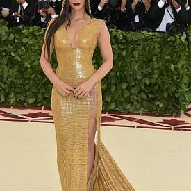 Актрисата и модел Оливия Мън бе облечена в дръзка рокля-ризница без ръкави, чиито драперии върху тялото наподобяват течност. Златистата дълга ризница с дълбоко деколте и отвор отстрани е поддържана от верижки от златисти халки, под които прозира кожата.