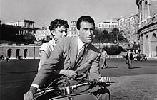 """Една страхотна класика от миналия век. През 1953 г. режисьорът Уилям Уайлър създава """"Римска ваканция"""". Филмът проследява историята на красивата принцеса Ан (Одри Хепбърн), която е на екскурзионна обиколка през няколко европейски столици. Пътуването и е широко отразявано от медиите и следва стриктна програма за посещения и срещи. Една вечер, отегчената принцеса решава да се измъкне от протокола и се впуска инкогнито сред улиците на нощен Рим, където обстоятелствата я срещат с американския журналист Джо Брадли (Грегъри Пек)."""
